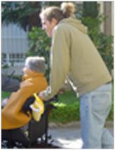 Joven ayudando a persona mayor en silla de ruedas